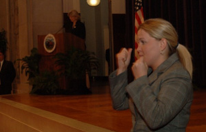 Image of interpreter signing in front of a stage.