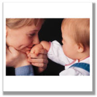 Picture of young girl kissing baby's hand.